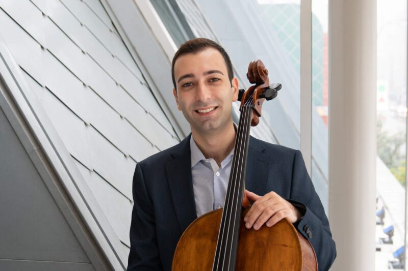 Headshot of Vardan Gasparyan standing in front of a window with a cello