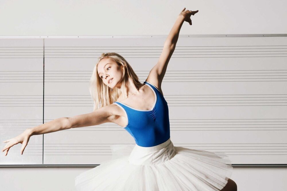 Sircey Smith poses with her arms outstretched, wearing a blue leotard and a white tutu