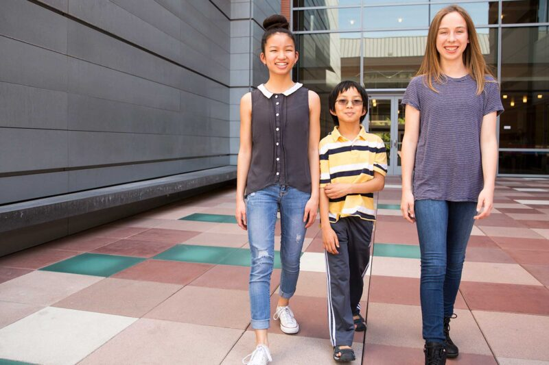 Three students of varying ages walking across the Colburn plaza