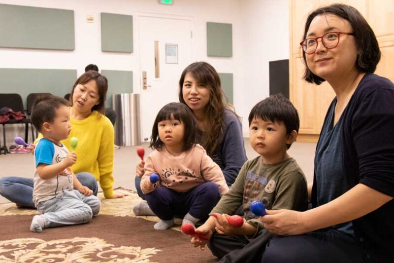 Mothers and children in sitting on ground in Early Childhood classroom