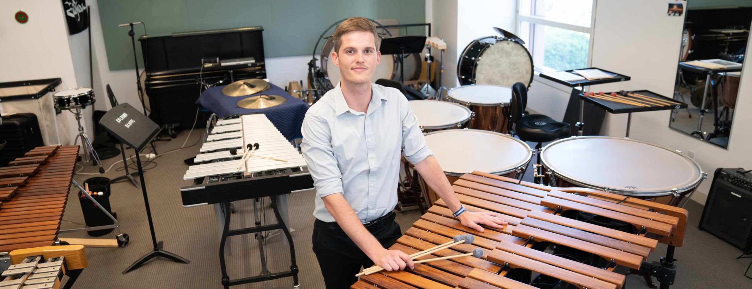 Percussionist with mallets sitting down around marimbas and timpani