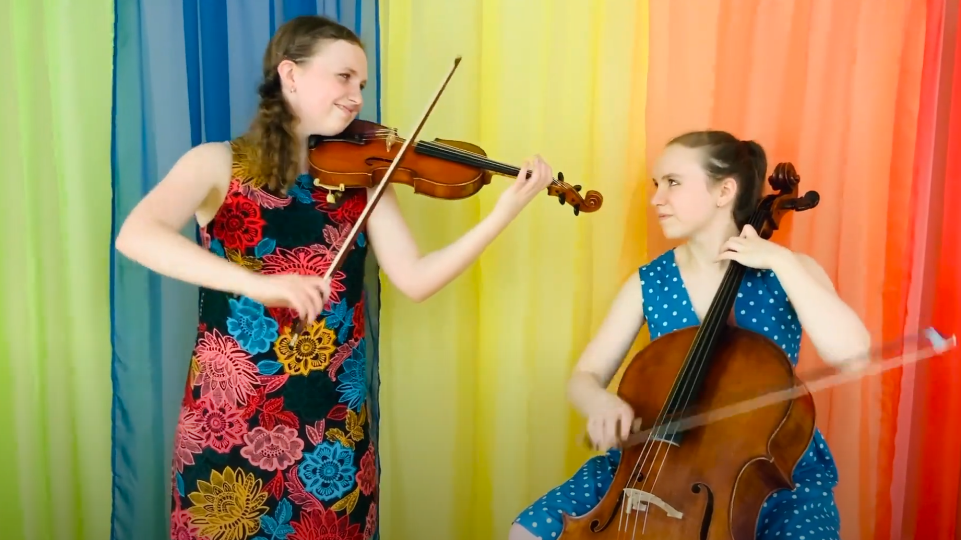 Violinist Charlotte and cellist Olivia Marckx wearing colorful dresses performing against a rainbow backdrop