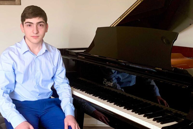 Ashot Ter-Martirosyan sitting in front of a piano