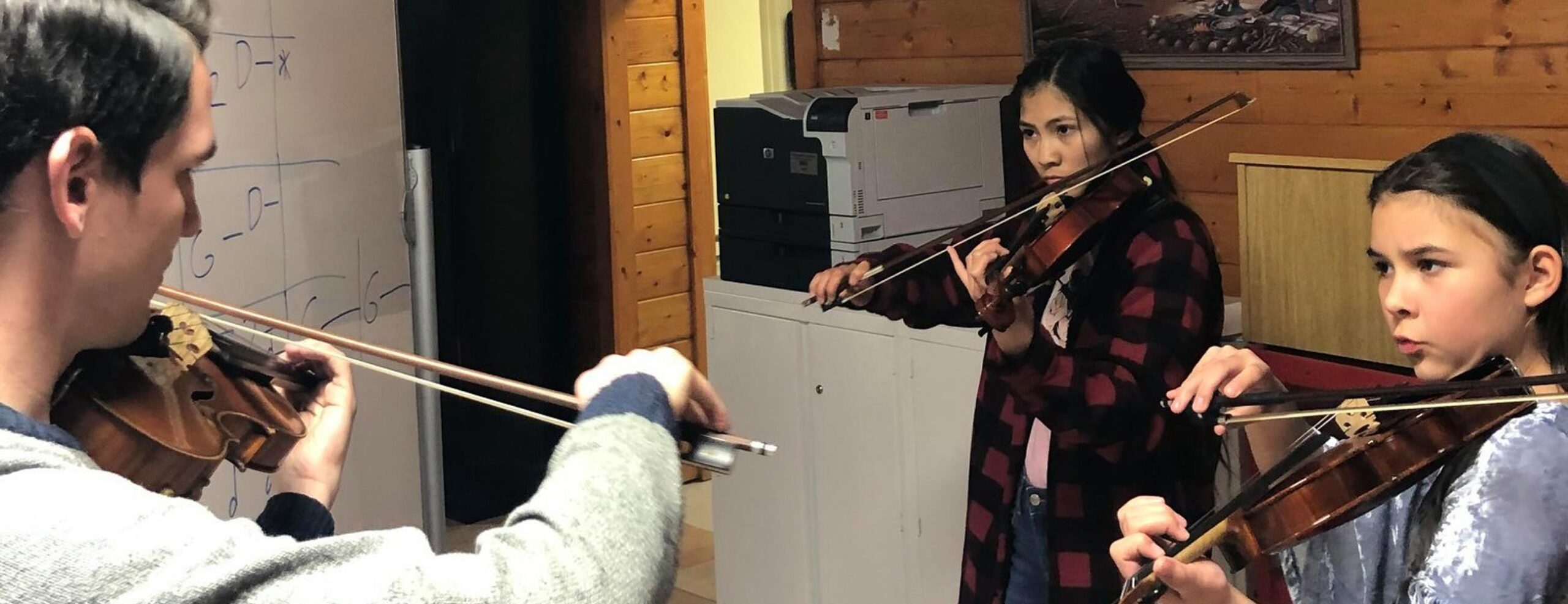 Violinist Gregory Lewis teaching two violin students on Navajo reservation
