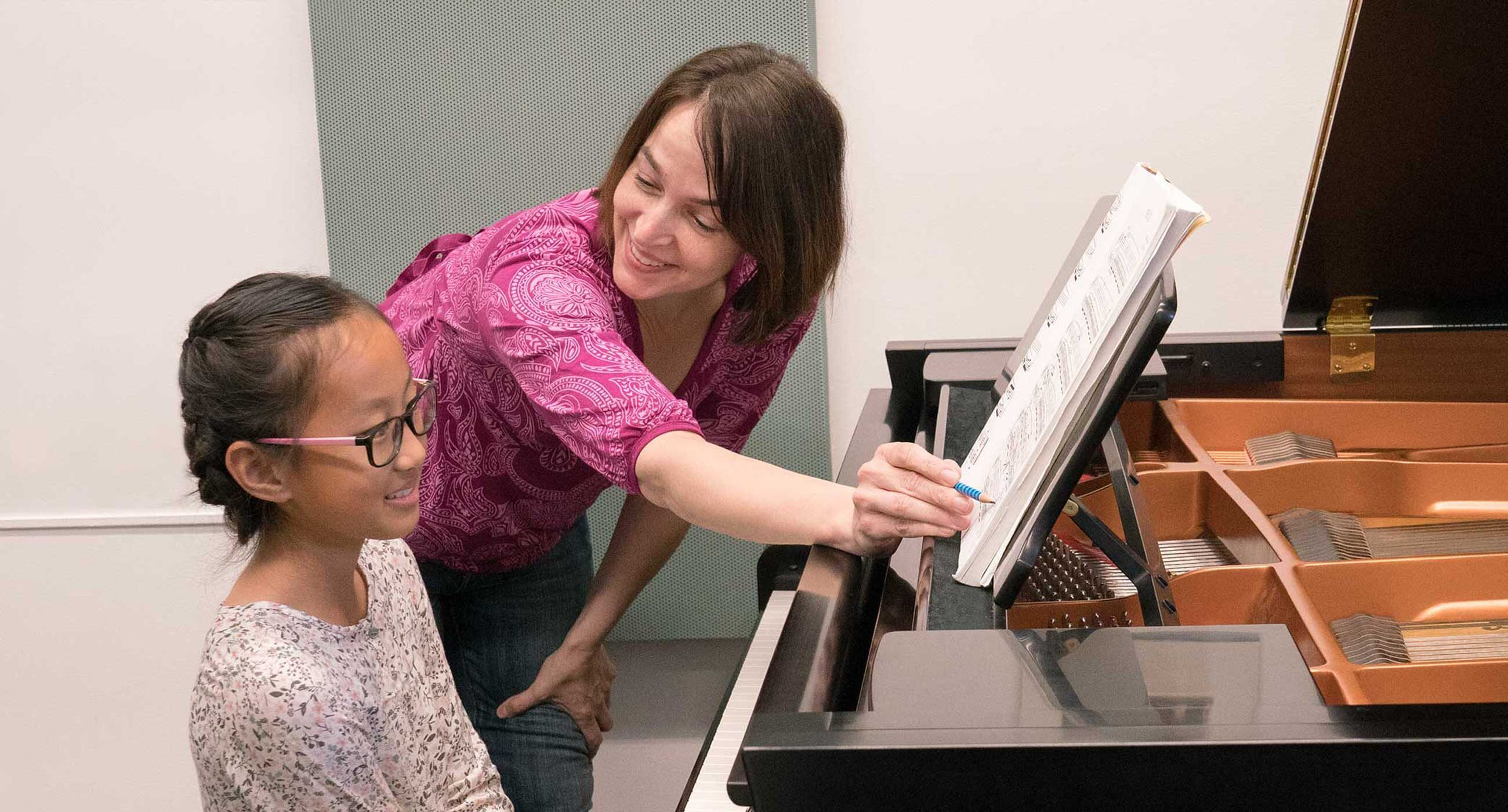 Teacher standing next to a student at a piano