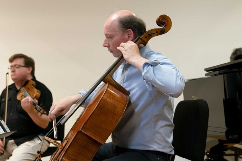 Clive Greensmith playing cello next to a piano with violinist in background