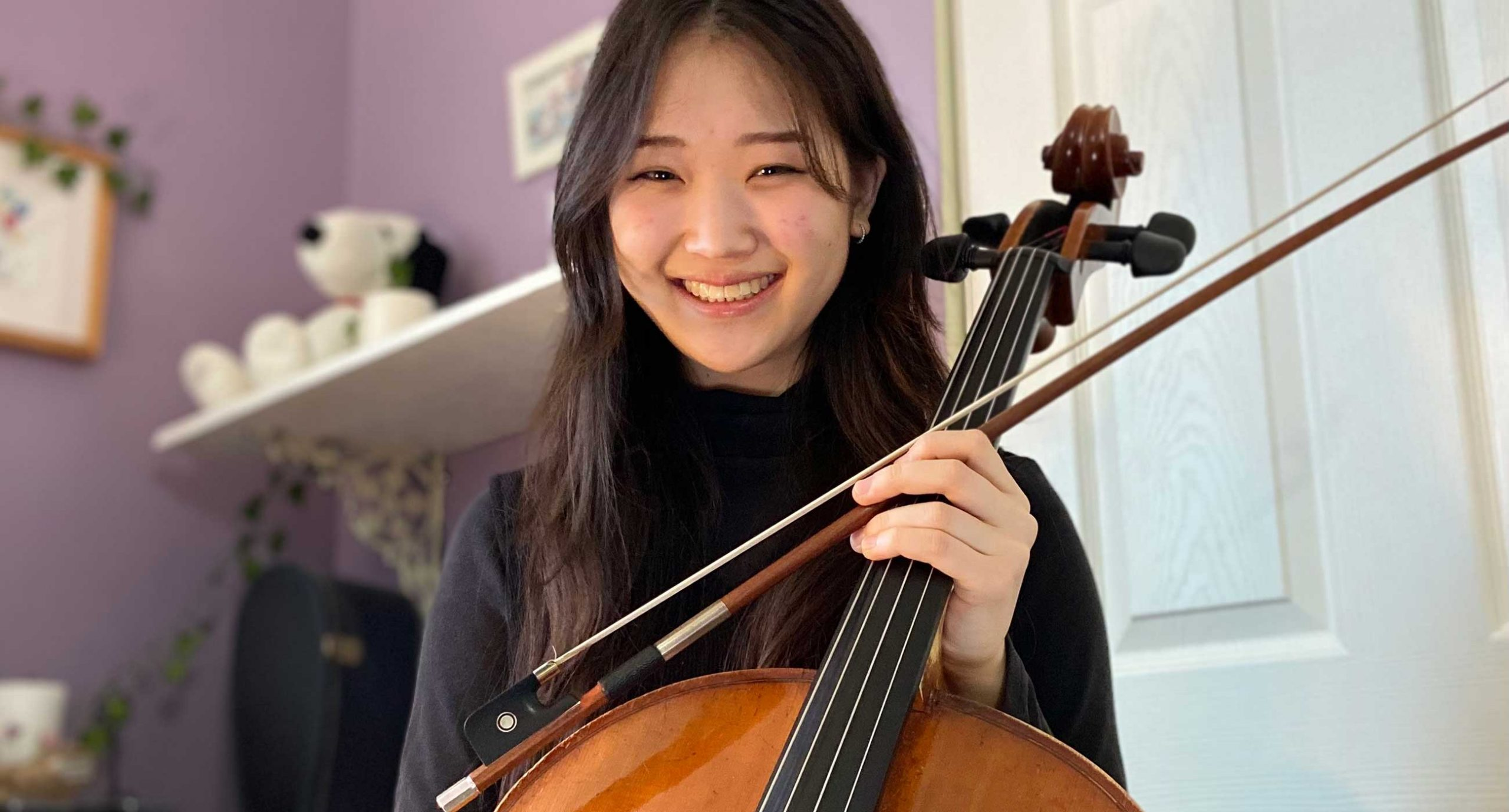 Mei Hotta holding a cello and smiling