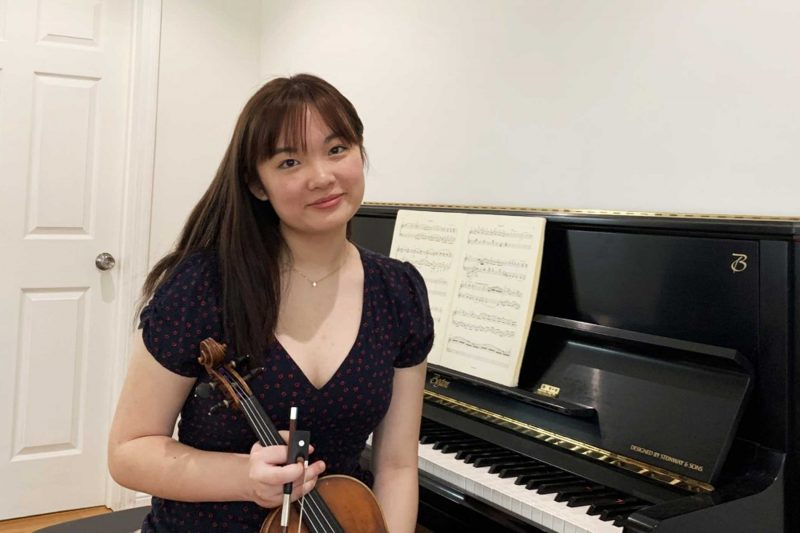 Scarlett Chen holding a violin sitting at a piano
