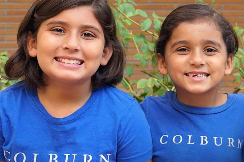 Two young students wearing blue Colburn tshirts smiling