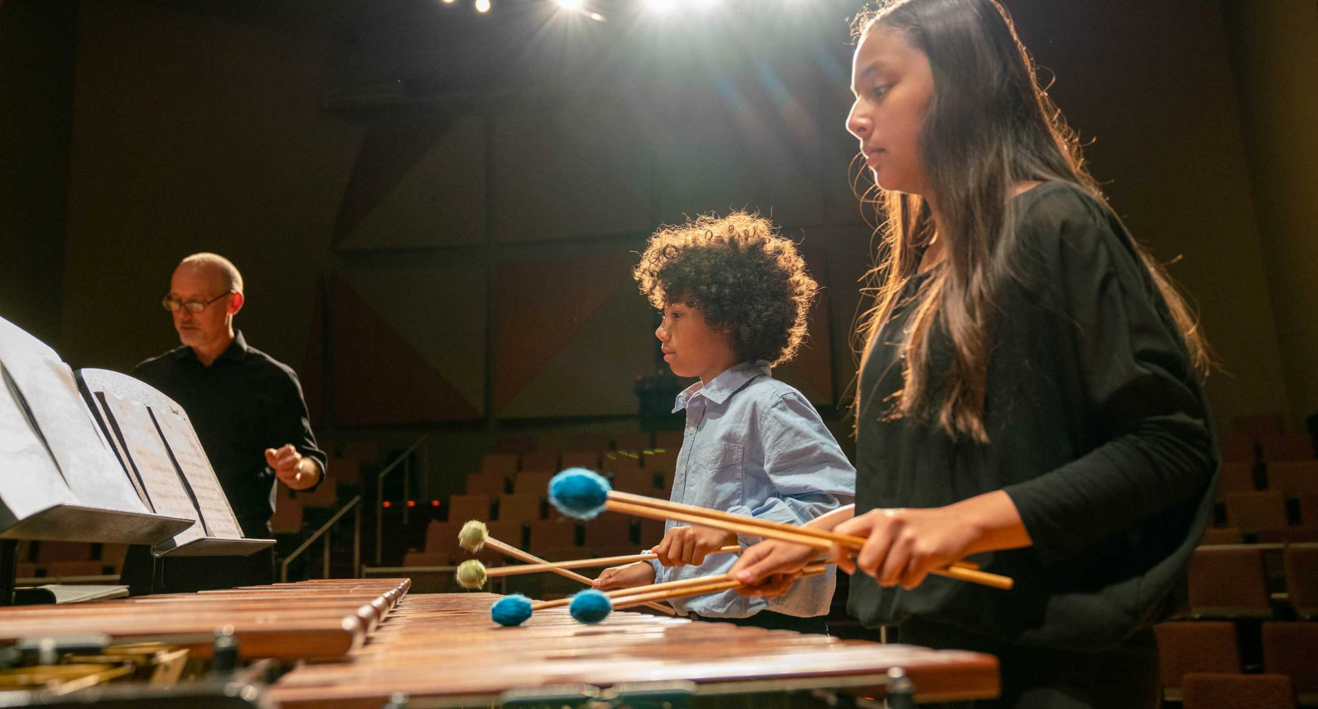 Two students playing marimba on stage with teacher in background