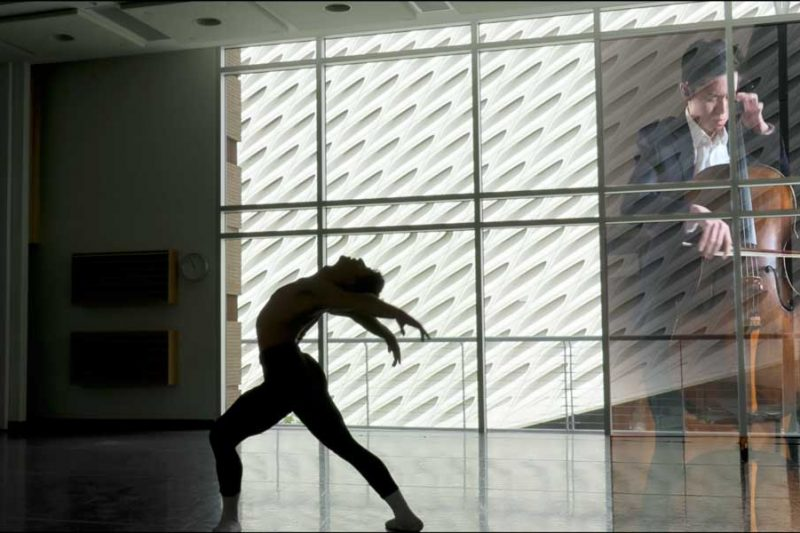 Dancer posing in studio with cellist playing in background