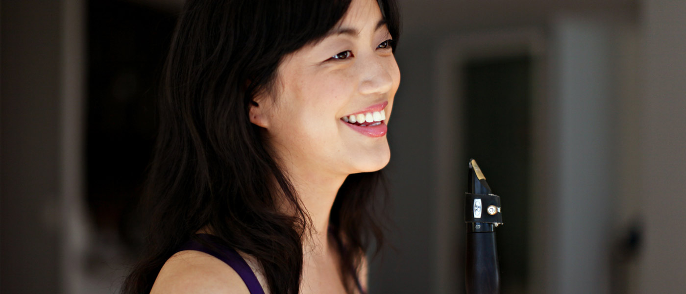 Alicia Lee smiling and holding a clarinet