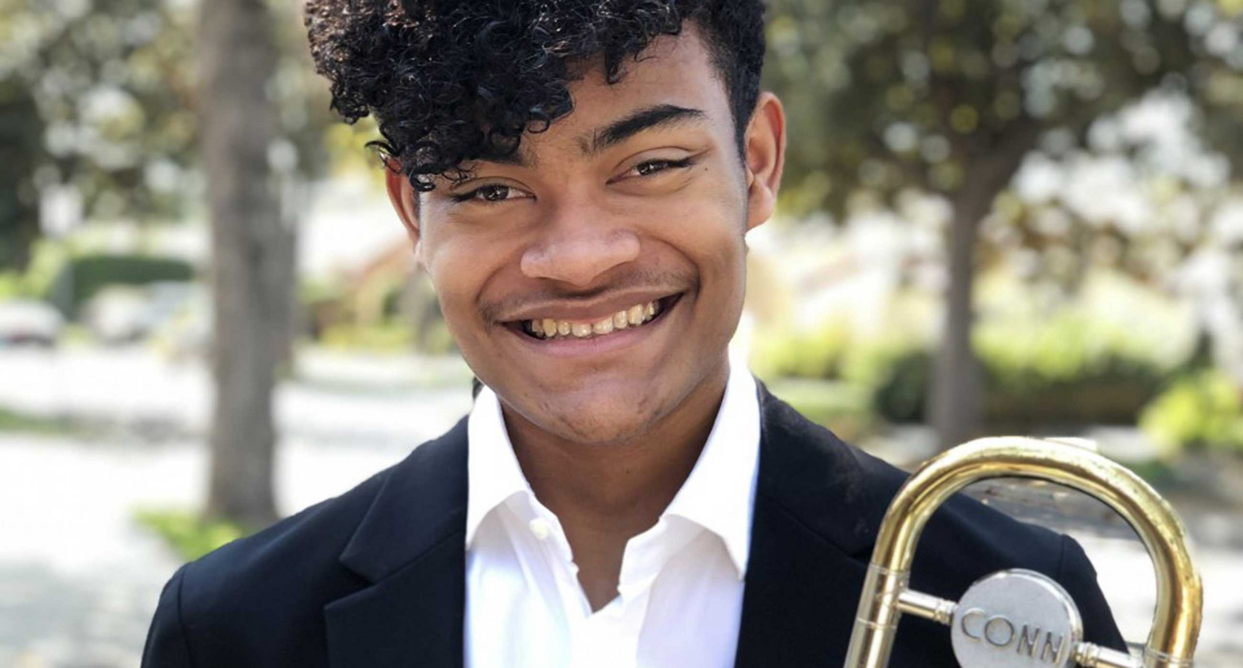 Elijah Alexander standing outside holding a trombone