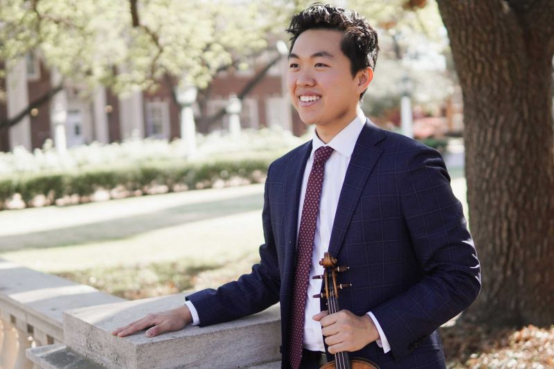 Hao Zhou wearing a suit holding a violin smiling