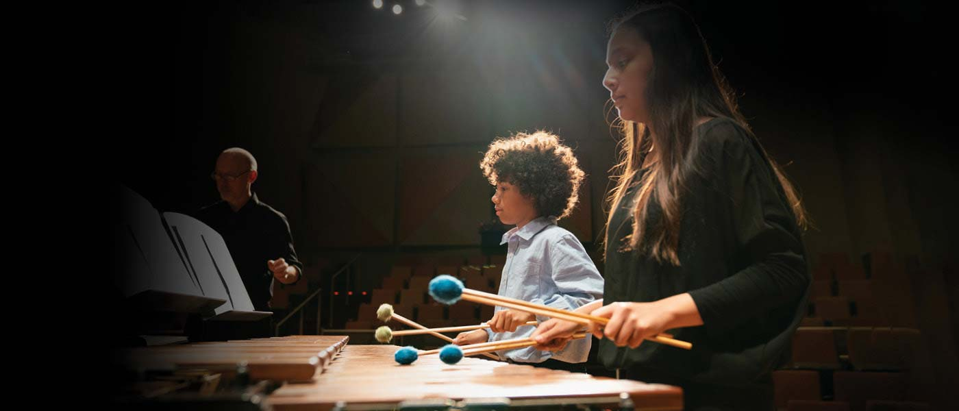 Girl and boy with playing marimba with mallets in hands on stage, teacher Ken McGrath in background