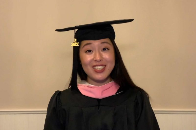 Alyssa Katahara wearing cap and gown with pink stole smiling