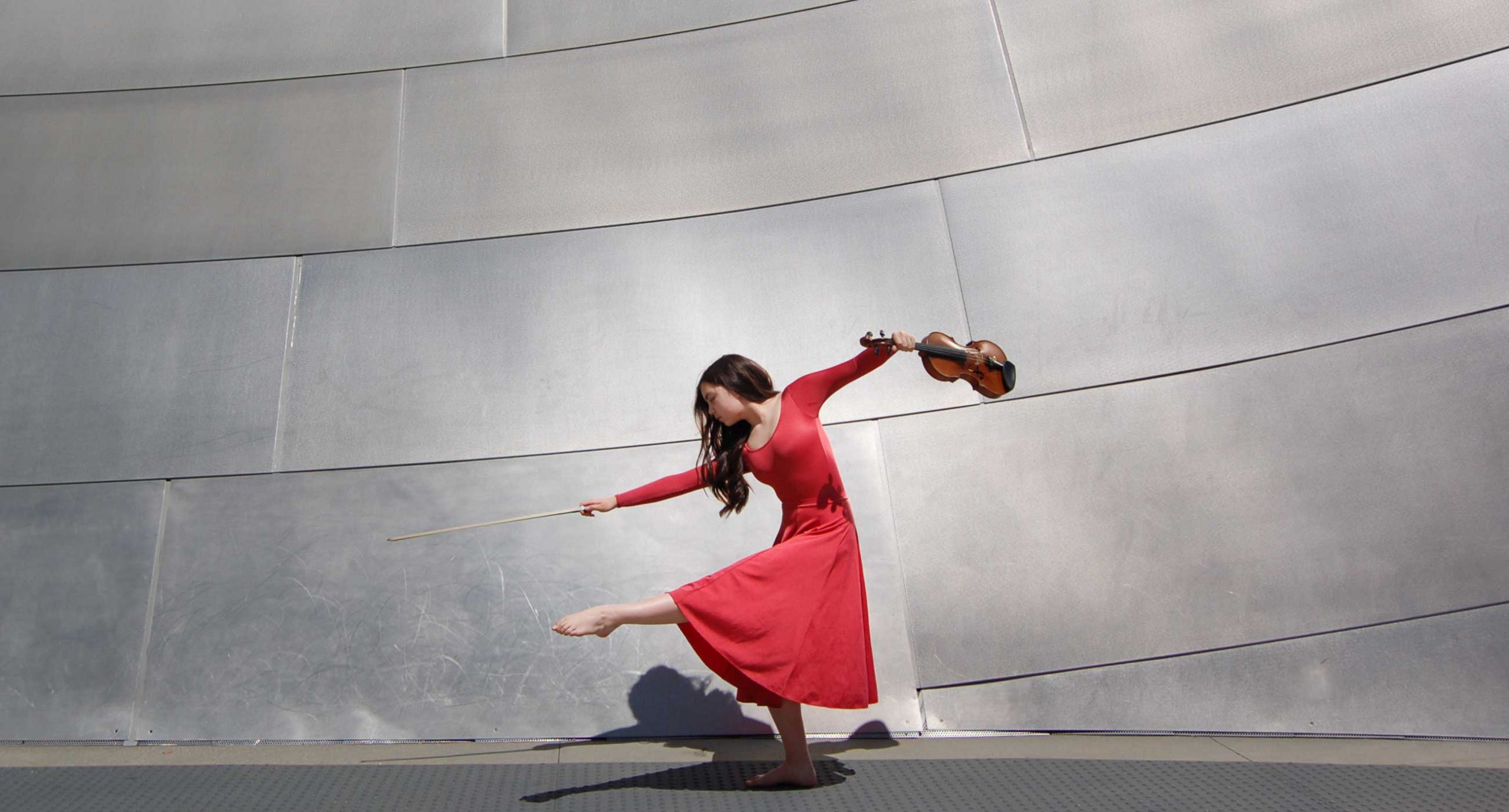 Holly Lacey wearing a red long sleeve dress posing with a violin in one hand, standing in front of a silver metal wall