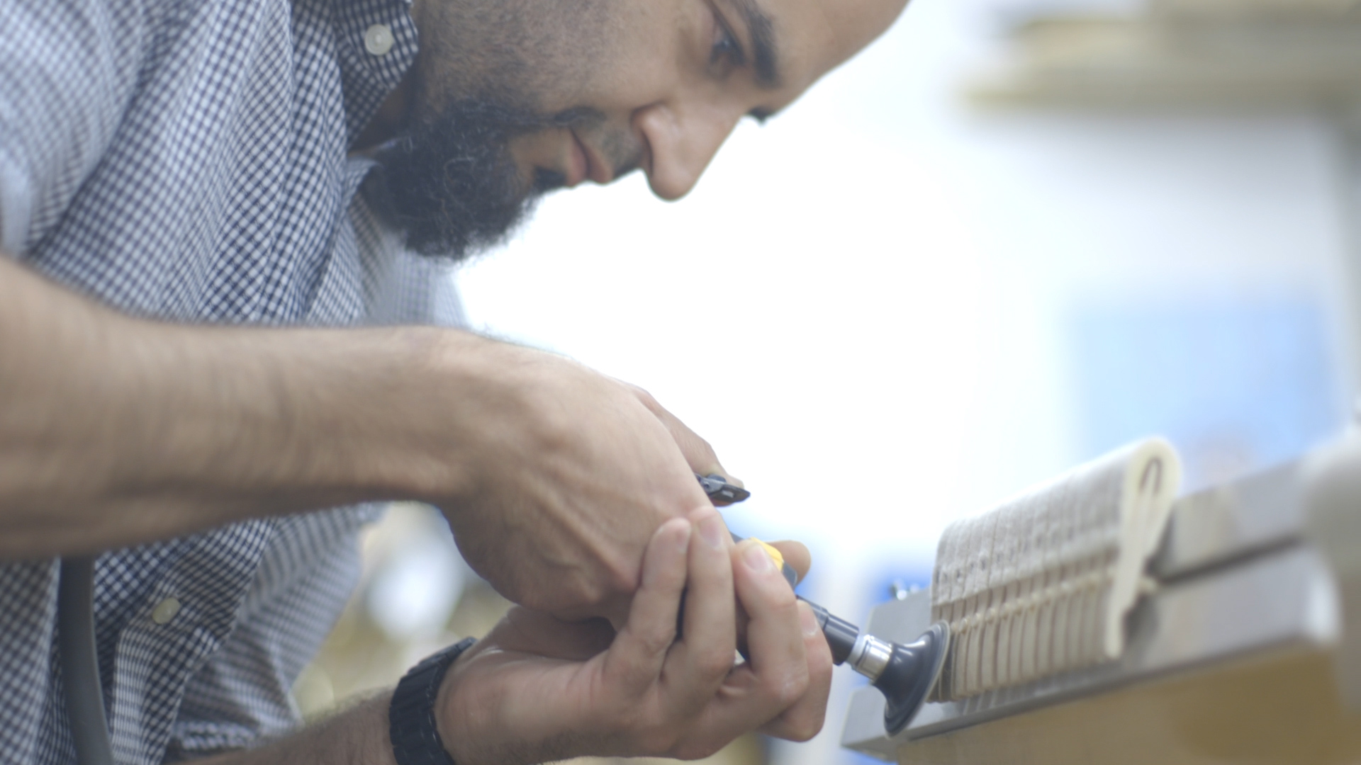Neema Pazargad uses a power tool while repairing piano parts