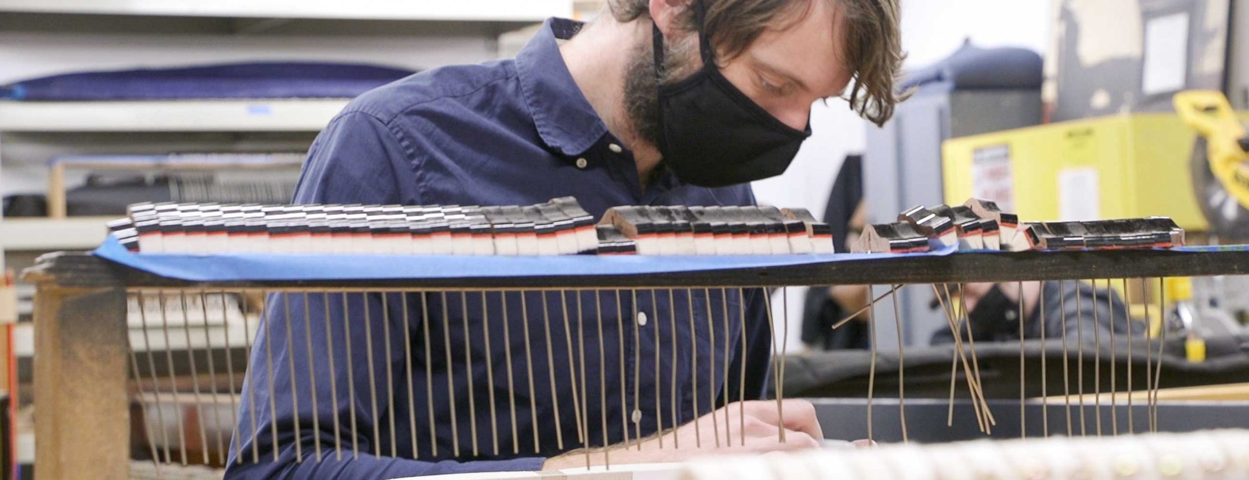 Man wearing face mask working on exposed piano strings in workshop
