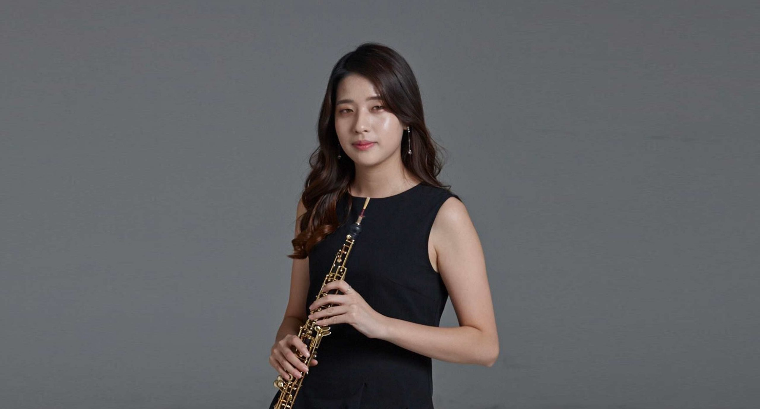 Korean woman with long black hair holding a oboe wearing a black dress against a grey background