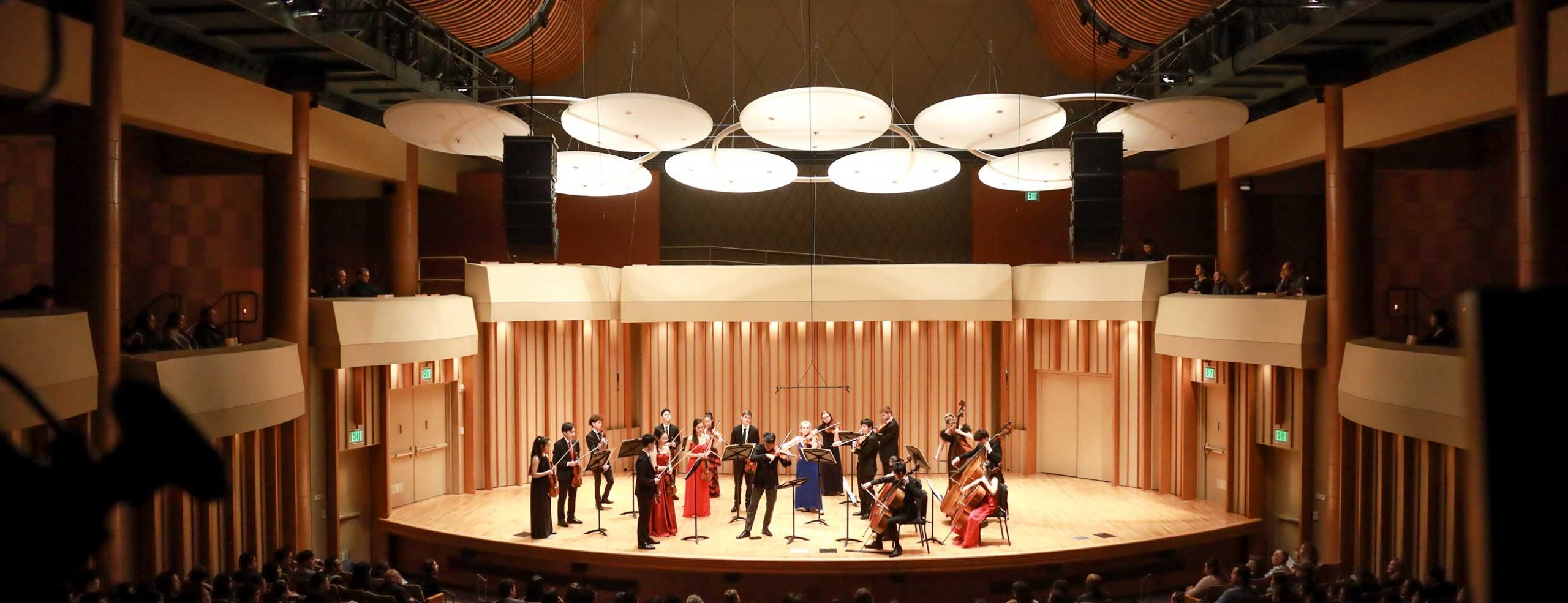 Chamber orchestra in formal dress standing on Zipper Hall stage with full audience