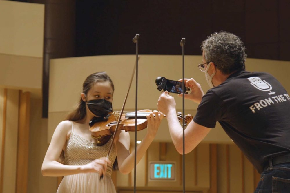 Violinist on Zipper Hall stage being photographed by man in From the Top tshirt