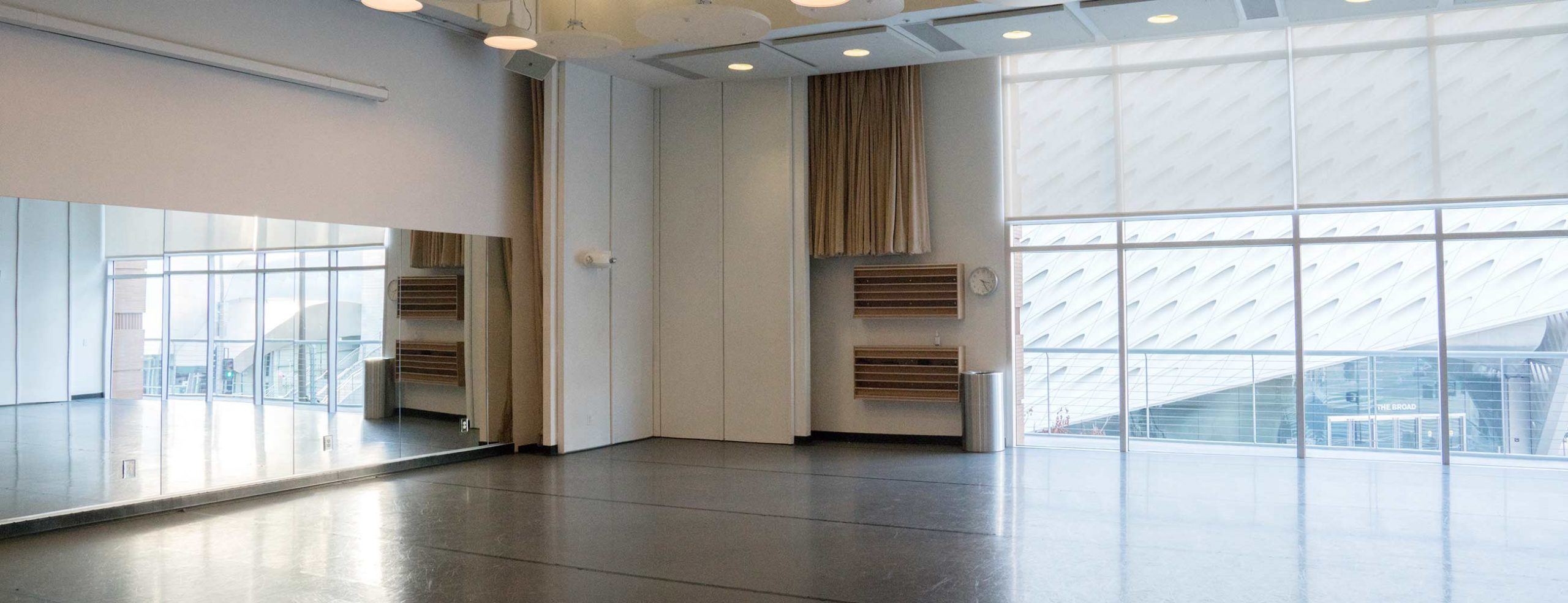Empty dance studio with The Broad museum visible through window