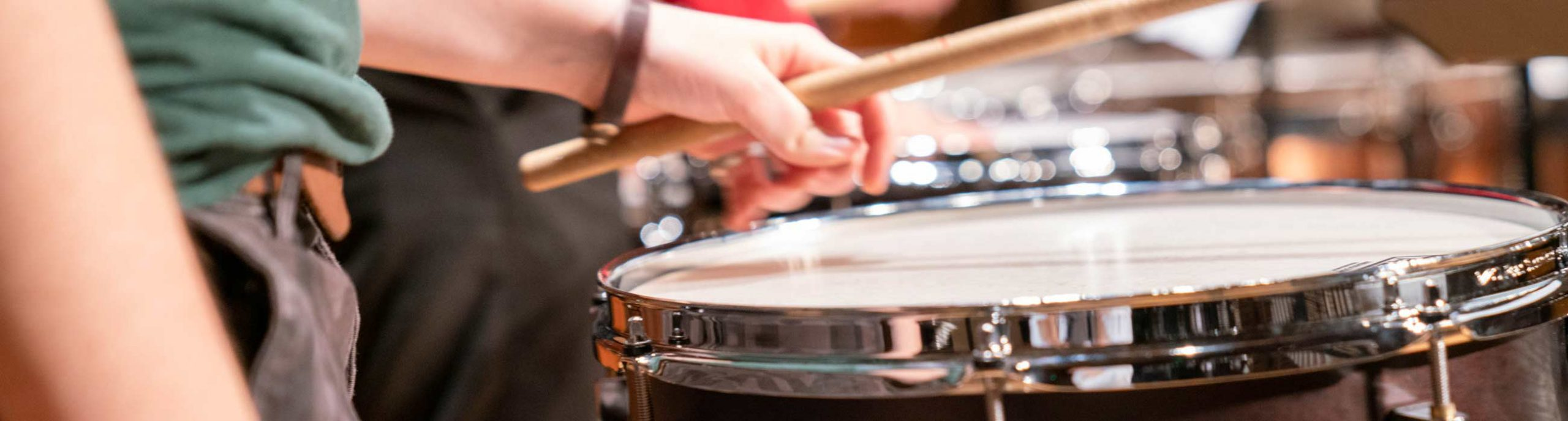 Close up of hand holding mallet above drum