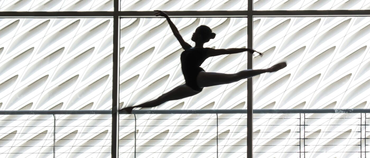 Silhouette of female dancer jumping with The Broad in the background