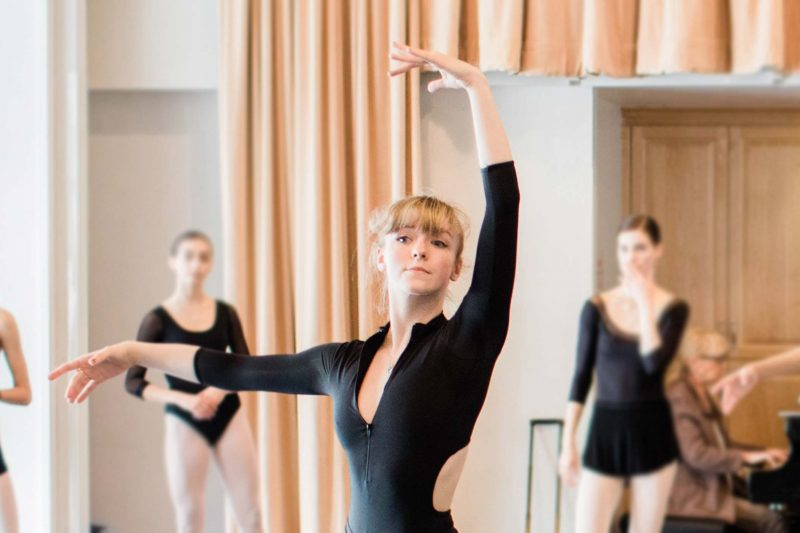 Dancer Niamh Perrins with arms posed in studio with other dancers in background