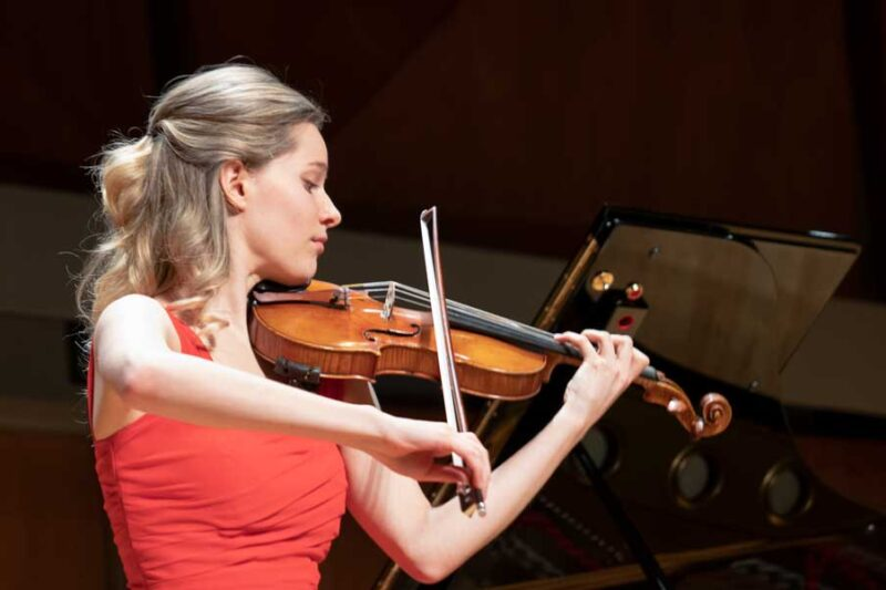 Violinist wearing a red dress playing on stage