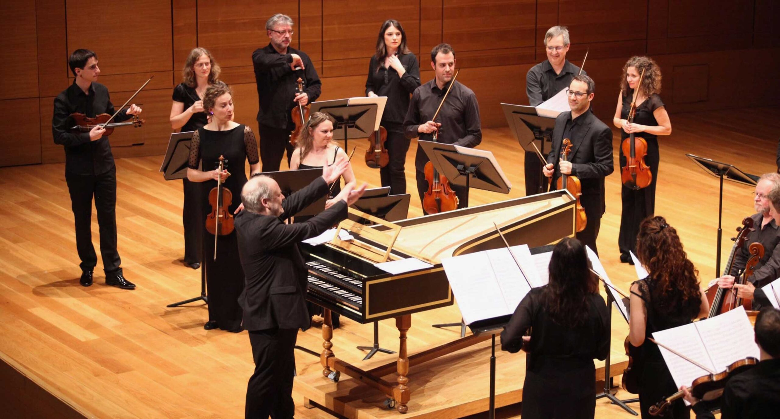 Dunedin Consort musicians on standing on stage with instruments