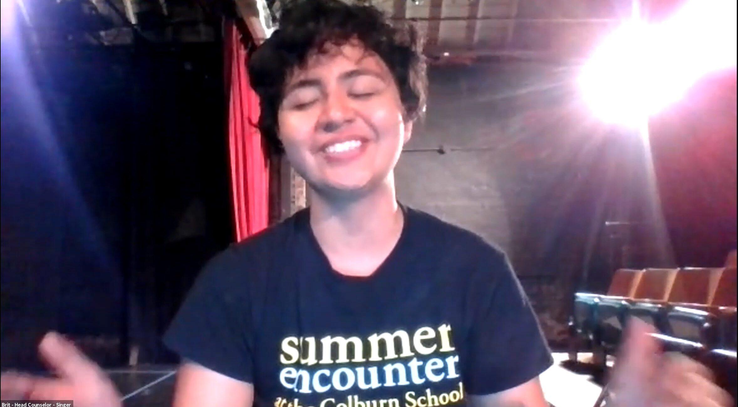 Zoom screenshot of person wearing black Summer Encounter tshirt singing