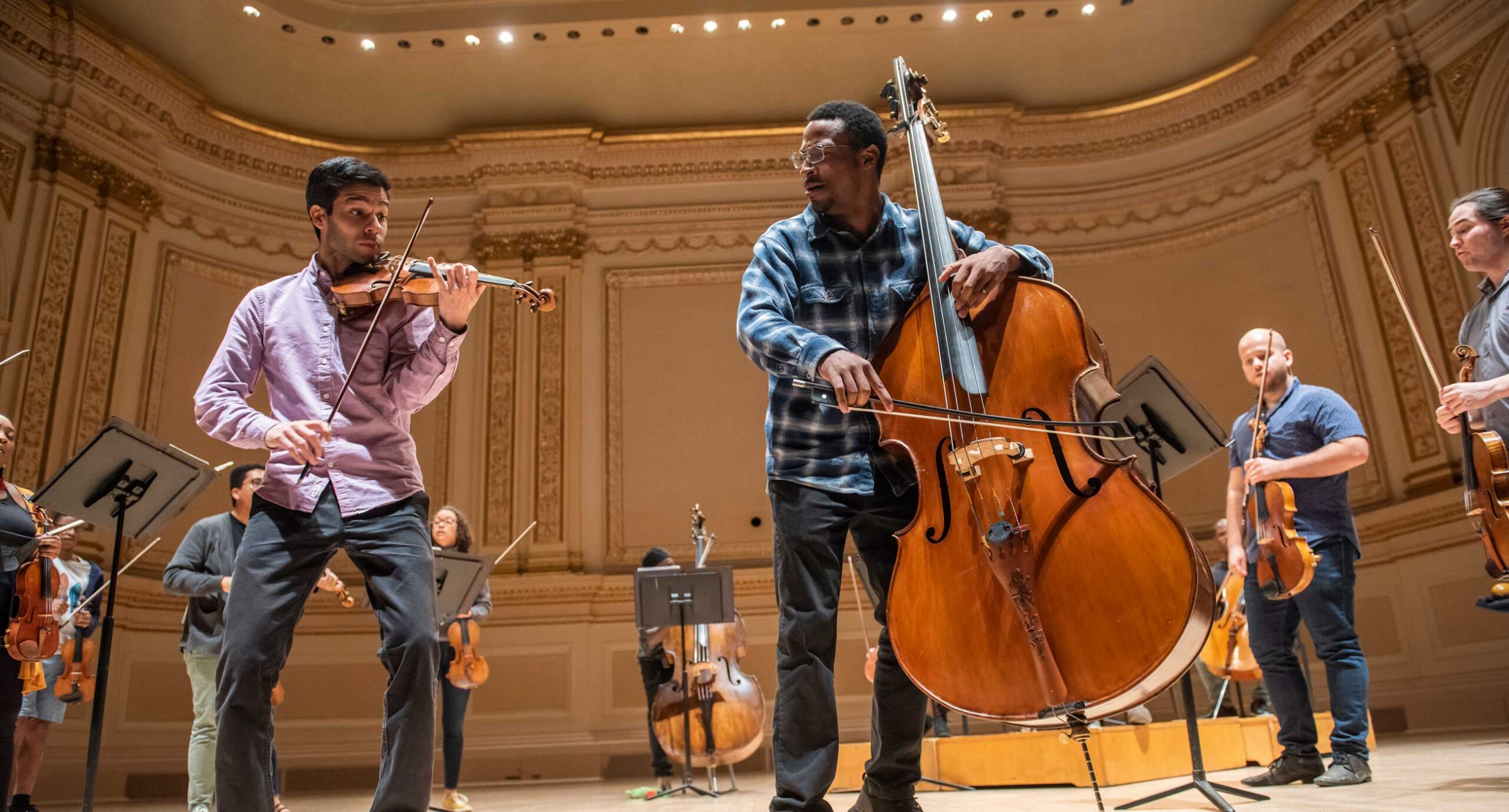 Violinist and cellist playing together on stage