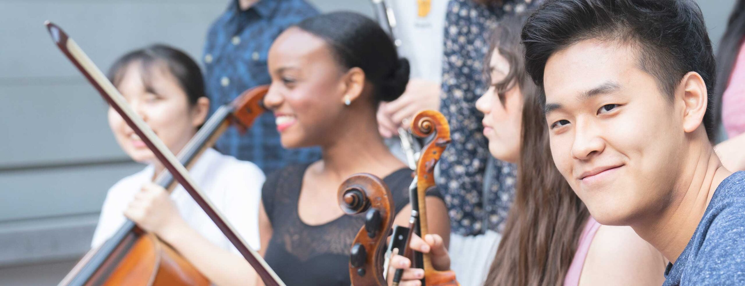 Asian student holding violin sitting to the right of Asian student with cello and Black dancer
