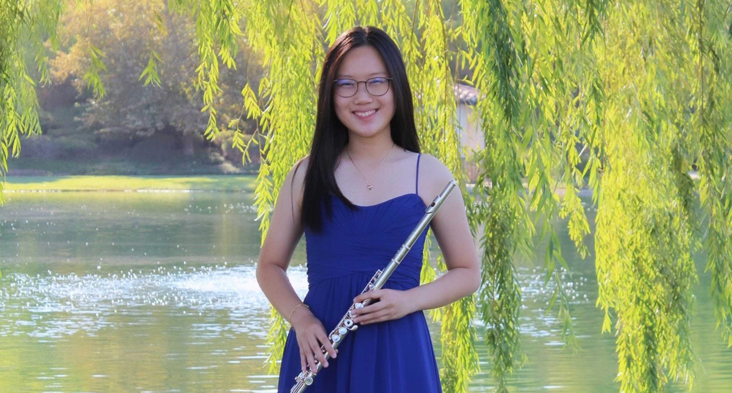 Celine Chen wearing a blue dress holding a flute, standing in front of a pond with tree branches with green leaves