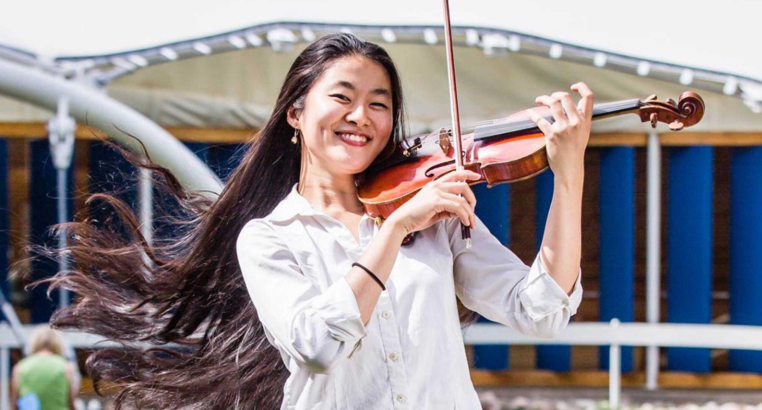 Kako Miura playing violin outside, smiling