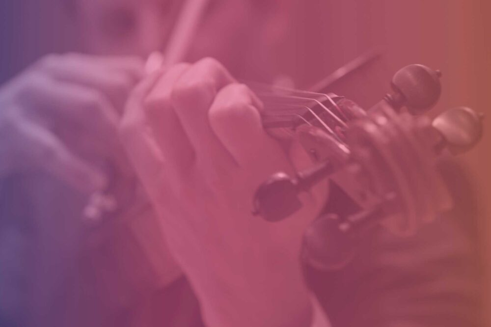 Purple, pink, and orange gradient colored photo of violist playing