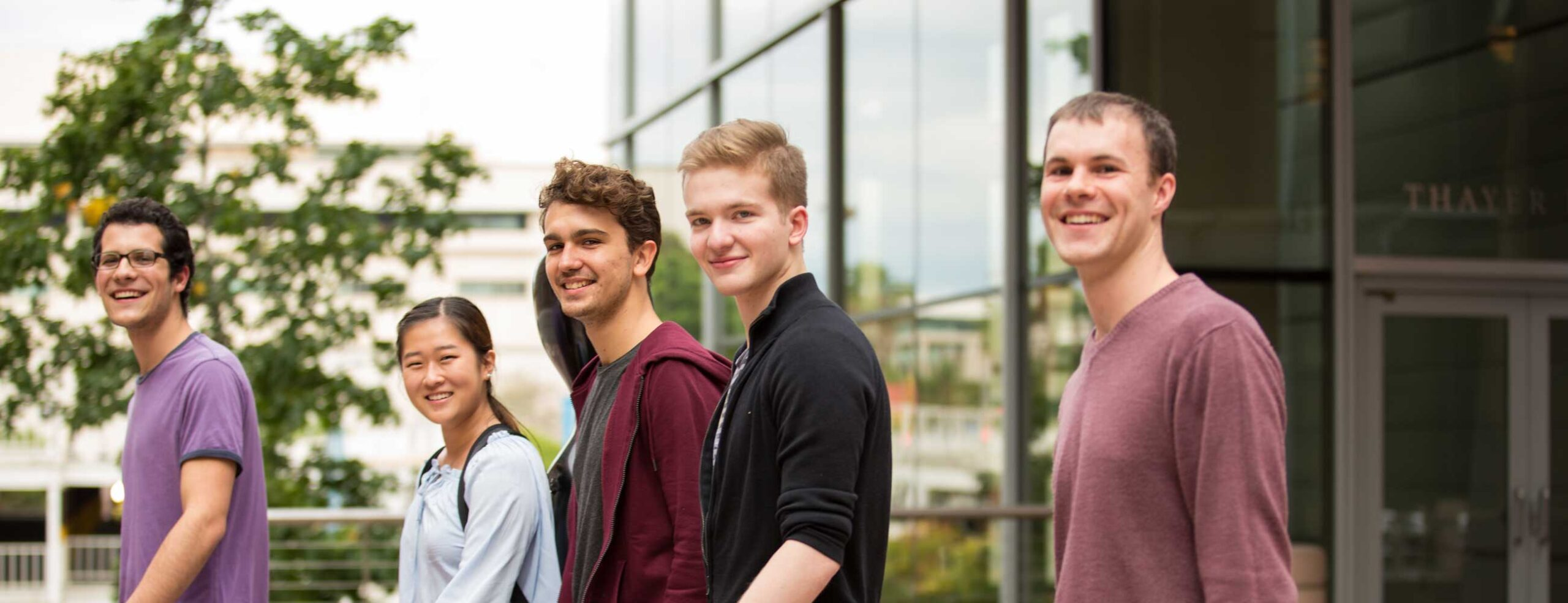 Group of college age students smiling and looking at camera outside in front of glass building